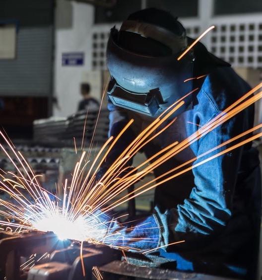 Welder welding metal in workshop with sparks